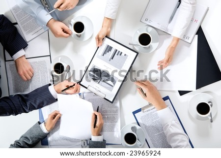 Image of hands of working businesspeople at meeting