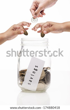 image of hands putting coin into glass bottle, saving concept - stock photo