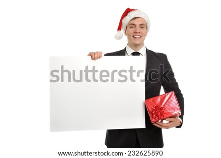 Image of handsome business man in Santa cap holding gift box and blank message. Sale, buying, Xmas gifts, presents etc. concept. Isolated on white background. - stock photo