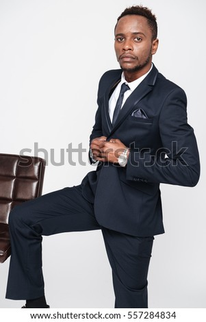Image of handsome businessman standing in studio. Isolated over white background. Look at camera.
