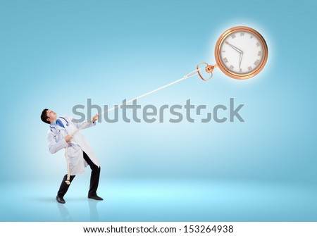 Image of handsome doctor pulling clock with rope - stock photo