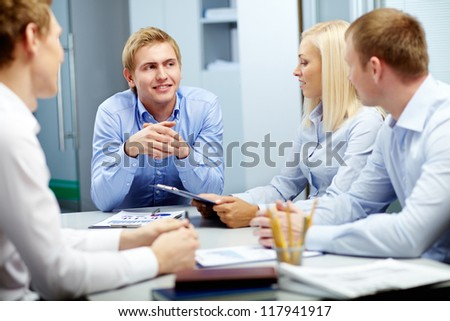 Image of handsome leader listening to employees at meeting