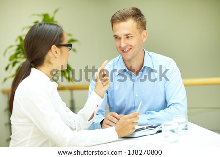 Image of handsome office worker smiling to his female colleague - stock photo