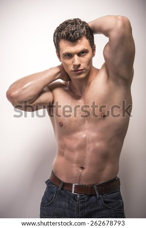 Image of handsome sexy young man in blue jeans isolated on white background.
