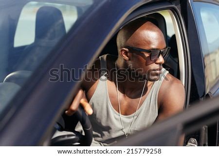 Image of handsome young man sitting in his car. Male model wearing sunglasses in a car. Afro american man.  - stock photo