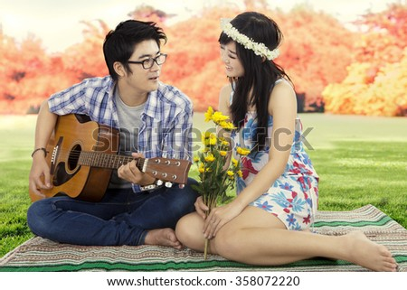 Image of handsome young man sitting on the autumn park with his girlfriend while playing guitar