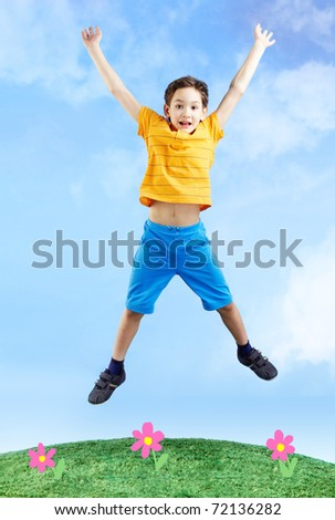 Image of happy boy jumping on the grass and looking at camera - stock photo