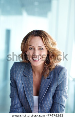 Image of happy businesswoman looking at camera