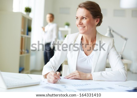 Image of happy businesswoman sitting at workplace - stock photo