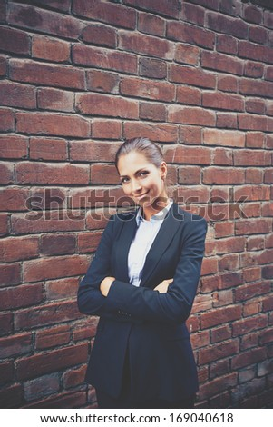 Image of happy businesswoman standing by brick wall and looking at camera