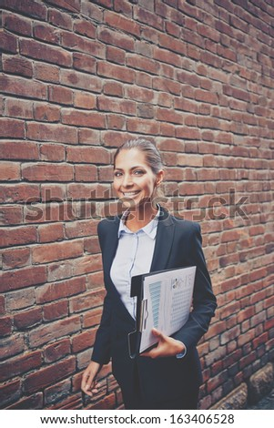 Image of happy businesswoman with document walking along brick wall