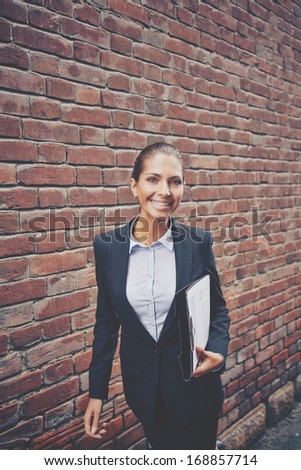 Image of happy businesswoman with document walking along brick wall - stock photo