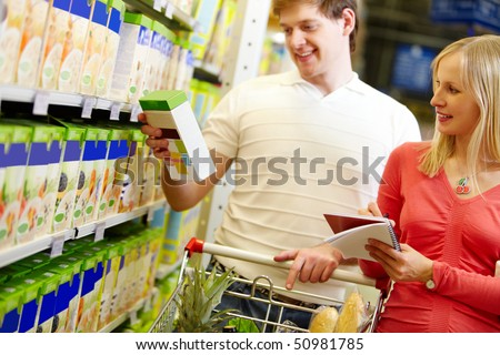 Image of happy couple choosing goods in supermarket