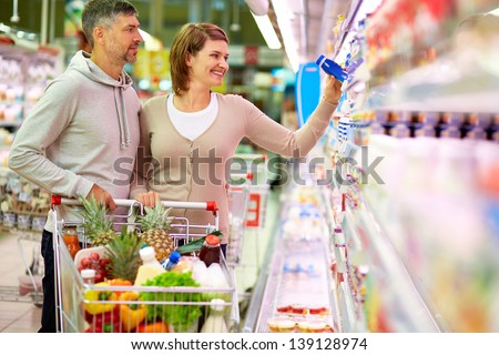 Image of happy couple with cart choosing products in supermarket - stock photo