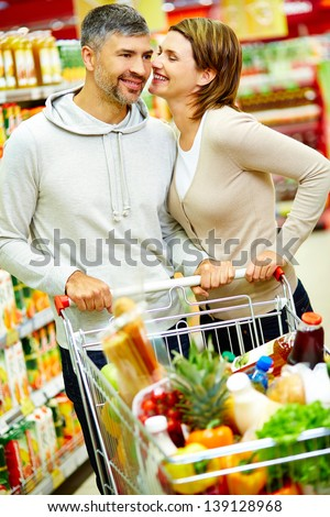 Image of happy couple with cart flirting in supermarket - stock photo