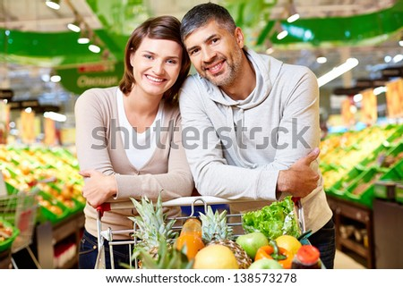 Image of happy couple with cart full of products looking at camera in supermarket - stock photo