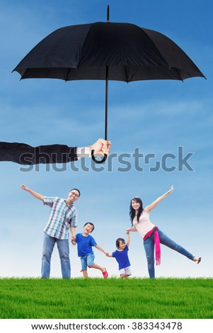Image of happy family having fun on the meadow under umbrella. Life and family insurance concept - stock photo