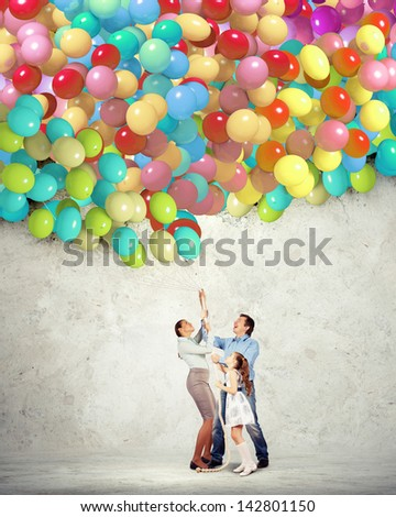 Image of happy family holding bunch of colorful balloons - stock photo