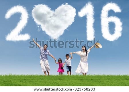 Image of happy family running at field while enjoying new year holiday under cloud shaped numbers 2016