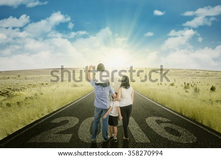 Image of happy family walking together on the road with numbers 2016 and bright sun light - stock photo