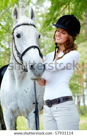 Image of happy female grooming purebred horse outdoors - stock photo