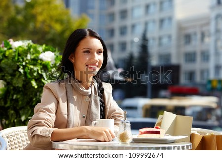 Image of happy female in open air cafe having coffee with cake in urban environment - stock photo