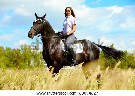 Image of happy female in sunglasses sitting on purebred horse outdoors - stock photo