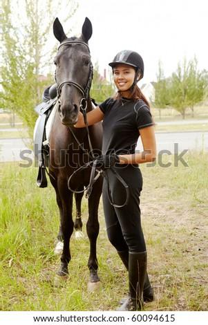 Image of happy female jockey with purebred horse outdoors - stock photo
