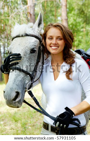 Image of happy female looking at camera with horse near by - stock photo
