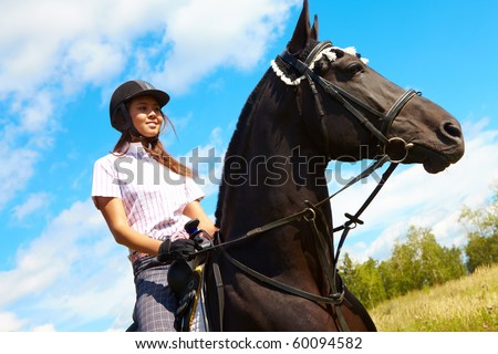 Image of happy female on purebred horse outdoors - stock photo
