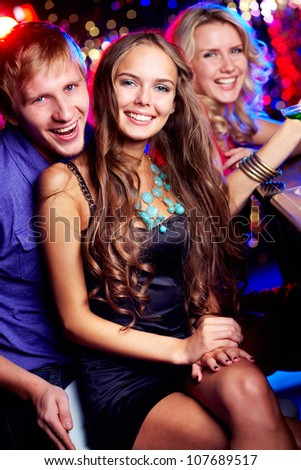 Image of happy friends looking at camera in bar