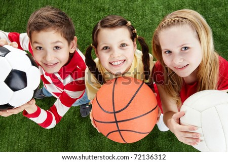 Image of happy friends on the grass with balls looking at camera