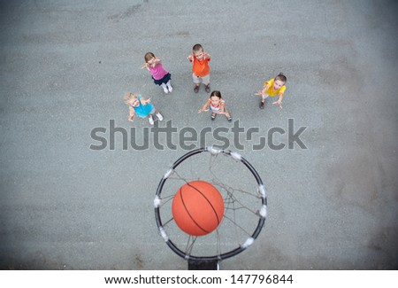 Image of happy friends playing basketball on sports ground - stock photo