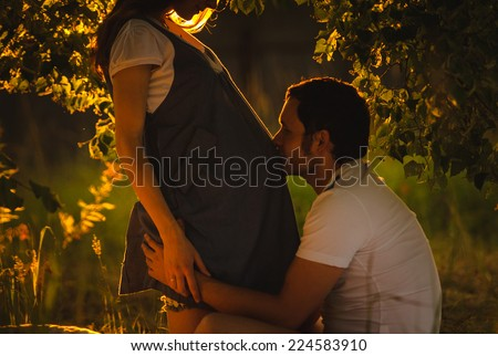 Image of happy future dad kiss the belly of his beautiful caucasian pregnant wife relaxing on green grass in the evening. Young family is resting in the garden or park into the sunset. - stock photo
