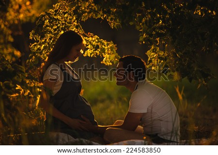Image of happy future dad touching the belly of his beautiful caucasian pregnant wife relaxing on green grass in the evening. Young family is resting in the garden or park into the sunset. - stock photo