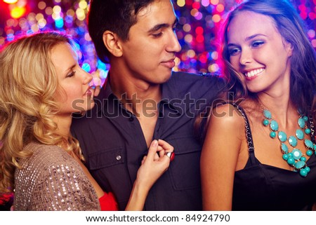 Image of happy girls and guy spending time together at party