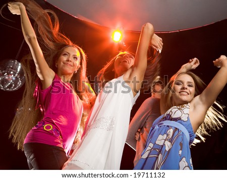 Image of happy teenagers raising their arms while dancing at disco - stock photo