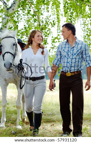 Image of happy woman surrounded by purebred horse and her sweetheart during walk