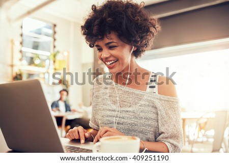 Image of happy woman using laptop while sitting at cafe. Young african american woman sitting in a coffee shop and working on laptop. - stock photo