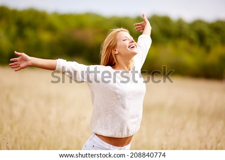 Image of happy woman with outstretched arms standing in field - stock photo