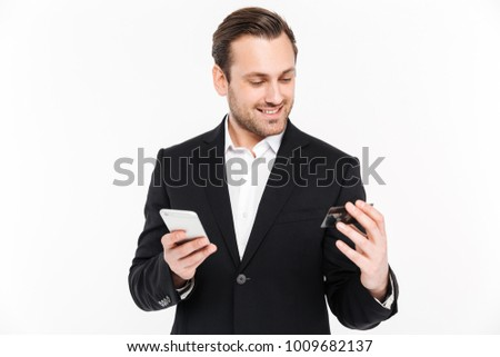 Image of happy young businessman standing isolated over white wall background. Looking aside using mobile phone holding credit card.