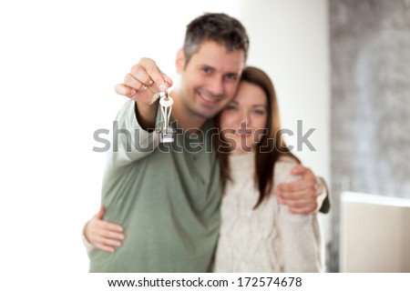 Image of happy young couple smiling and holding key ring, shallow depth of field focus on foreground - stock photo