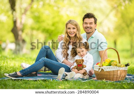 Image of happy young family having picnic outdoors. - stock photo