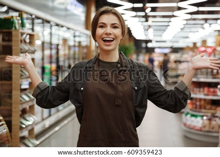 Image of happy young lady in supermarket standing and holding copyspace on hands. Looking at camera.