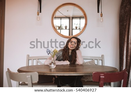Image of happy young woman with long hair dressed in sweater sitting at the table in cafe. Looking at camera.