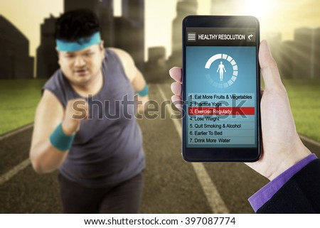 Image of healthy resolutions program on the smartphone screen with overweight person running at field