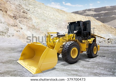 Image of heavy wheel loader with yellow color and a steel shovel on the mining site