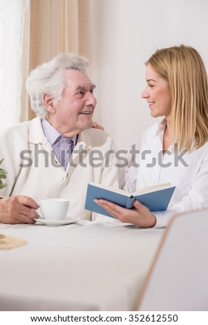 Image of helpful woman with disabled father - stock photo
