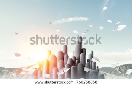 Image of high and huge stone columns located outdoors among flying paper planes with beautiful landscape on background. Wallpaper, backdrop with copyspace.