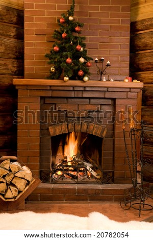 Image of hot fire in chimney with fir tree decorated before Christmas - stock photo